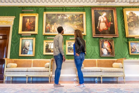 A young couple look at paintings in the Throne Room. The walls are lined with green silk damask and the paintings are hung in gold frames. Gold and grey details frame the walls and doors. A large rug covers the dark wooden floor.