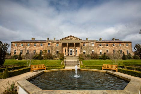 The South Front of Hillsborough Castle, surrounded by the gardens. A small fountain runs in the foreground