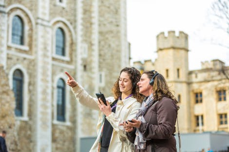 The White Tower, looking north-west. The image is focused on two young women visitors in the foreground, happily using digital video guide tour devices.