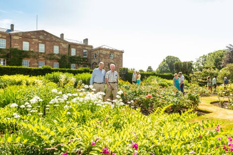 Two gentlemen and a group of visitors enjoy a wander through the Granville Garden on a sunny Summers day at Hillsborough Castle. The westerly facade of the castle is visible in the background.
