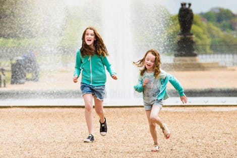 Two female children playing next to the fountain in the gardens of Hampton Court Palace. In the background there are benches and yew trees visible.