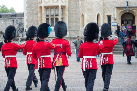 The backs of six soldiers from the Irish Guards are shown whilst walking.