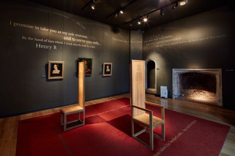 The Young Henry exhibition on display in the Wolsey Suite. Showing two wooden thrones chronicling the story of the early life of King Henry VIII and painted quotations on the walls of the room.