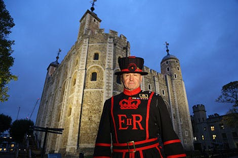 A Yeoman Warder stands outside the White Tower during a Twilight Tour or the Tower.