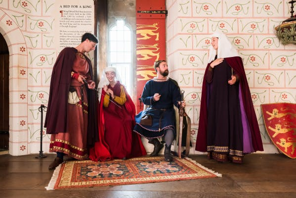 Medieval knights and ladies in the fashions of 1299, talking in the Medieval Palace.