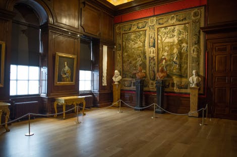 The wooden panelled Privy Chamber at Kensington Palace with tapestries on the walls and busts on the far side