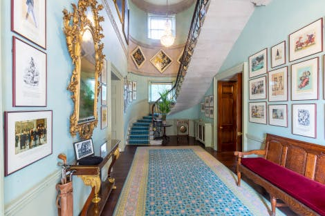 View of Stair Hall looking towards stairs that lead to the Royal Corridor. The walls are a soft blue and a large patterned rug covers most of the wooden floor. The walls are adorned with old political cartoons depicting the history of Irish and American politics. A gold-framed mirror hangs on the wall and a red-cushioned bench sits opposite.