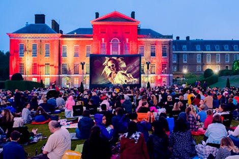Luna Cinema event at Kensington Palace, with crowds of people watching Rocketman on a summer's evening outdoors.
