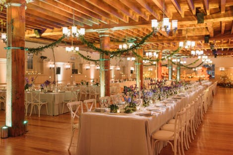 Long tables set up for dining in the Banqueting Suite set for dinner with garlands and flowers