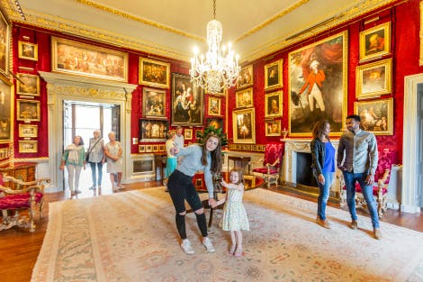 A group of visitors enjoying a viewing of the Red Room, one of Hillsborough Castle's State Rooms. Two young girls appear in the foreground along with a young couple. A small group of older ladies and gentlemen can be seen in the background having just entered the room. The walls are lined with a deep red silk damask and a variety of oil paintings in gold frames of various sizes fill the walls.