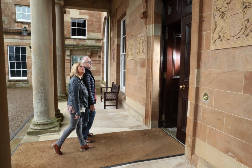 Man and woman couple walking towards State Entrance door of Hillsborough Castle