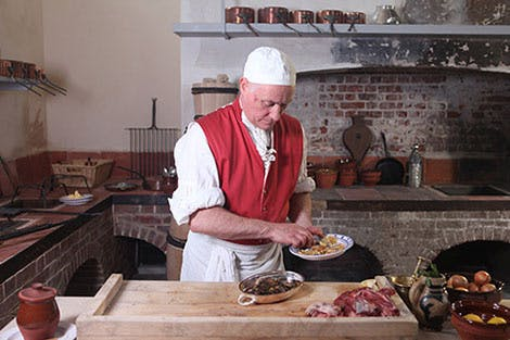 A Georgian cook in red and white overalls prepares food in the Royal Kitchens at Kew Palace