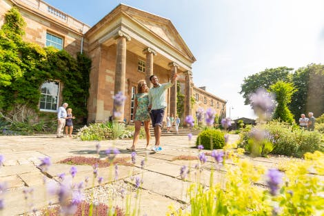 A young couple walking across the stone-flagged South Terrace in front of the South Façade of Hillsborough Castle. Other visitors can be seen in the background. The sun is shining and a blue sky hangs above. Purple lavender is just visible in the foreground.