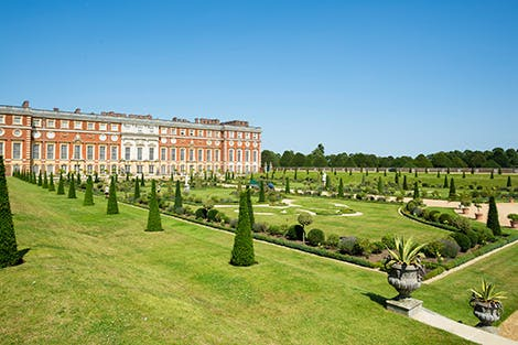 The Privy Garden at Hampton Court Palace, showing bright planting and baroque architecture under a clear blue sky