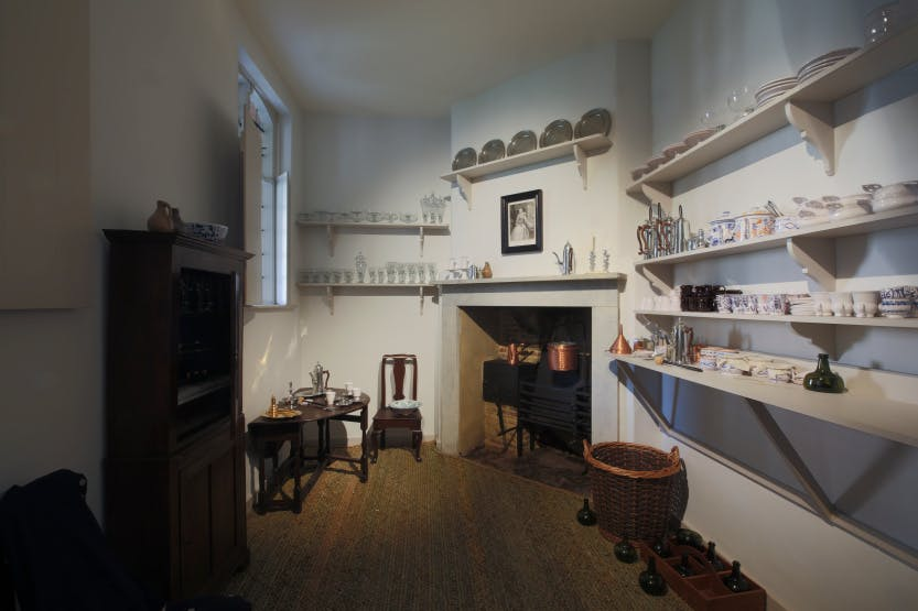 The 18th-century fixtures and fittings of the Chocolate Kitchen survive – visible is the Georgian fireplace and smoke jack within the chimney, a pair of charcoal braziers, plus a folding table, cupboard and shelves.