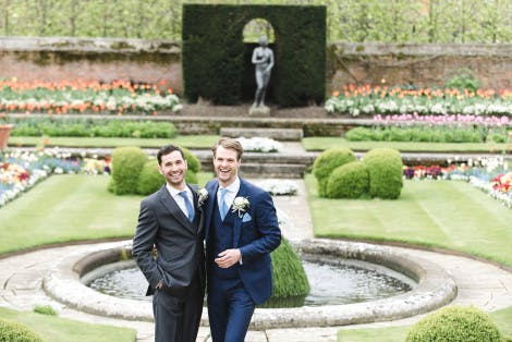 Grooms smile at the camera in front of a colourful green garden and pond feature