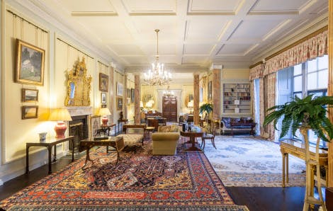 State Drawing Room with wooden floor and a variety of persian rugs and furniture from the Royal Collection. A variety of Irish art hangs on the sunny yellow walls. Marble-like pillars frame the room.