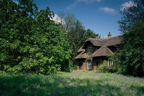 Queen Charlotte's Cottage surrounded by trees and garden under a blue sky
