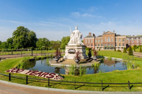 A floral display reading '200 years' outside the East Front of Kensington Palace, under a bright blue sky and surrounded by formal lawn. The palace is in the background.