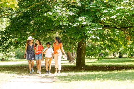 A family of two women, a boy and a girl walk through the Wilderness at Hampton Court Palace in the shade. The little boy is eating an ice cream and they are surrounded by greenery