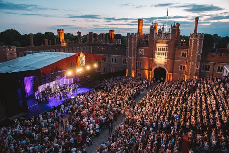 A music festival takes place in front of a huge crowd within the Tudor courtyard of Hampton Court Palace