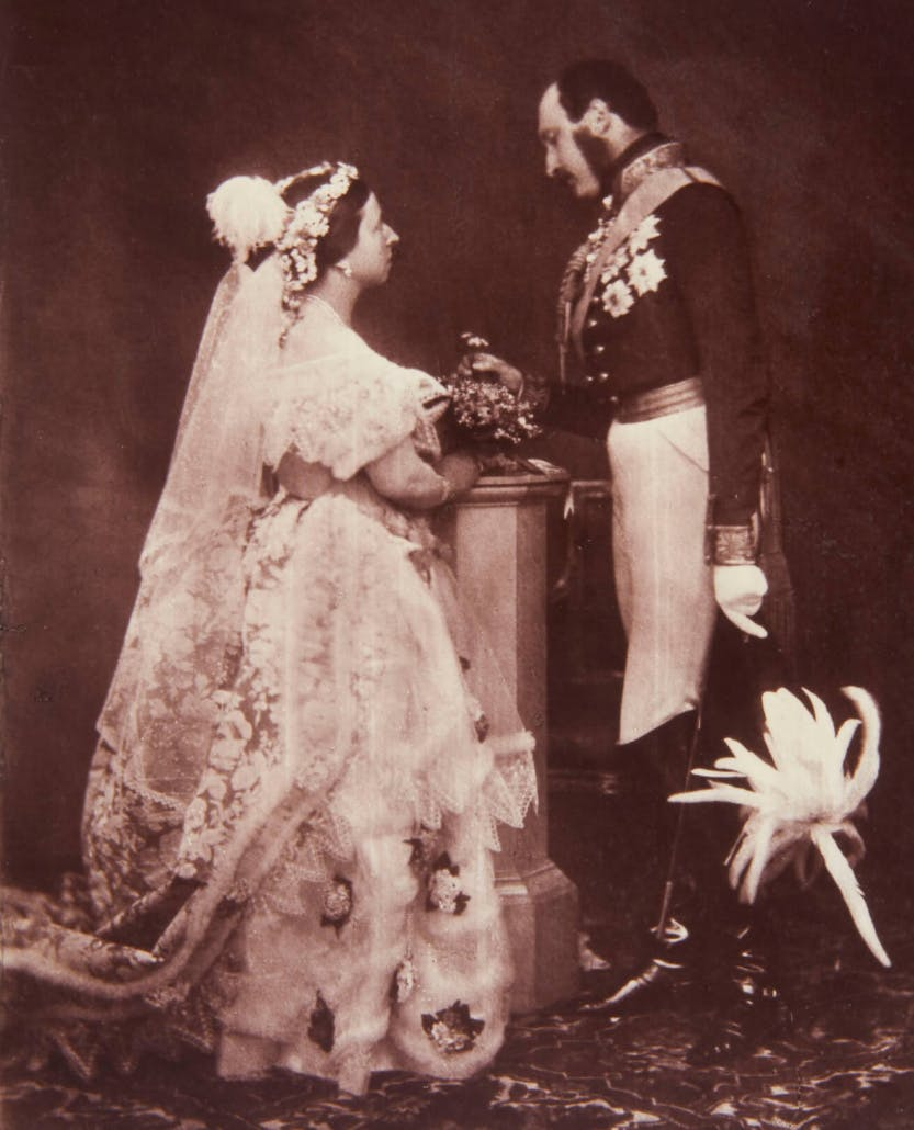 Photograph showing a full length portrait of Queen Victoria (1819-1901) and Prince Albert (1819-61), photographed at Buckingham Palace. Queen Victoria stands in right side profile and wears court dress. Prince Albert stands in left side profile, holding a feathered hat in his left hand and wears a uniform. There is a pedestal between them, with flowers upon it.