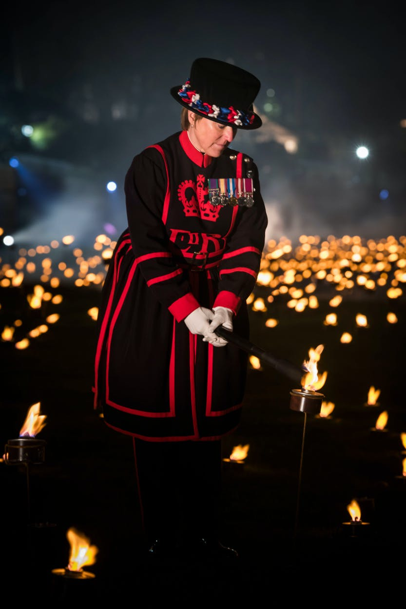 "The Tower Moat, showing Yeoman Warder Moira Cameron lighting an Armistice torch as part of her ceremonial duty at the ""Beyond the Deepening Shadow"" public event.   ""Beyond the Deepening Shadow: The Tower Remembers"" was a public act of remembrance to commemorate the centenary of the end of the First World War.  Each evening from 4 to 11 November 2018 the Tower moat was illuminated by 10,000 individual flames. The artistic installation included an exploration in sound of wartime alliances, friendship, love and loss. Beginning with a procession led by the Yeoman Warders, Armistice torches were lit to form a circle of light radiating from the Tower. A symbol of remembrance for the hundreds of thousands who died in the Great War."