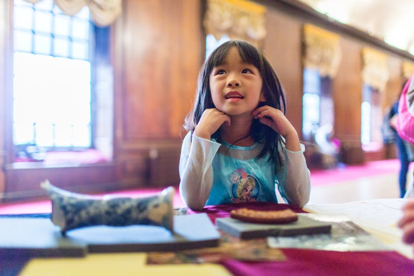 A young girl enjoys the family activities in a panelled historic room, surrounded by bright white light coming through the windows. She looks up at something on the other side of the camera and smiles.