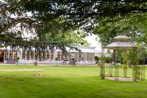 Walled Garden with green lawn and a garden room event space in the background. Foliage from trees hangs over the foreground of the image