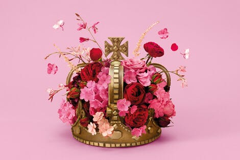 A gold crown sits on a bright pink background covered in pink flowers