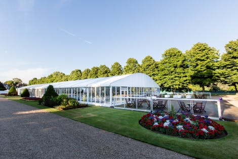 Event tent in the gardens of Hampton Court Palace surrounded by green trees under a blue sky