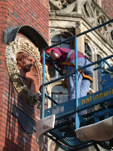 Conservator examining a terracotta roundel on the west front from a cherry picker