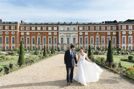 A bride and groom hold hands in front of the East Front of Hampton Court Palace, Surrey