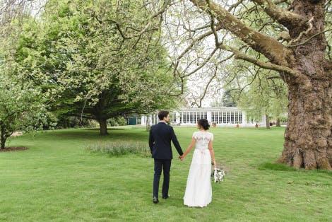Bride and groom in the garden in front of the Garden Room