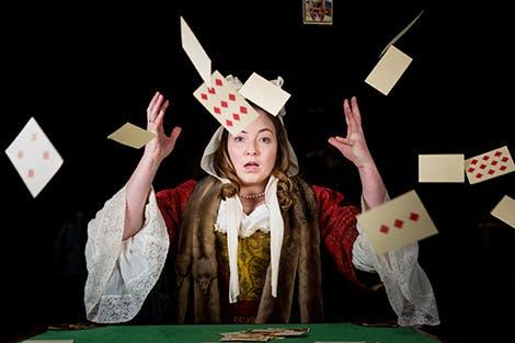 Live interpreter dressed as Georgian maid plays card games