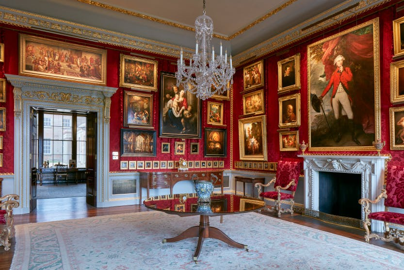 The Red Room at Hillsborough Castle with rich red walls and paintings.