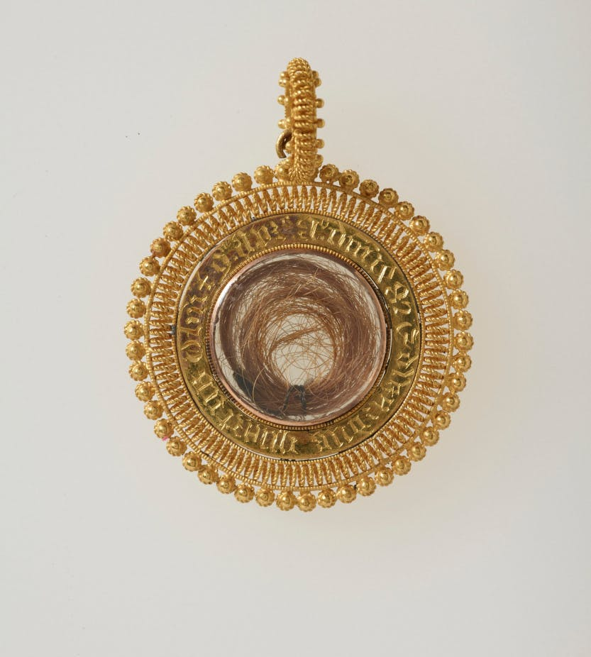 A circular gold filigree locket with Edward IV's lock of hair.