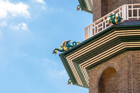 Green and gold dragons on the side of the Great Pagoda at Kew, surrounded by blue sky