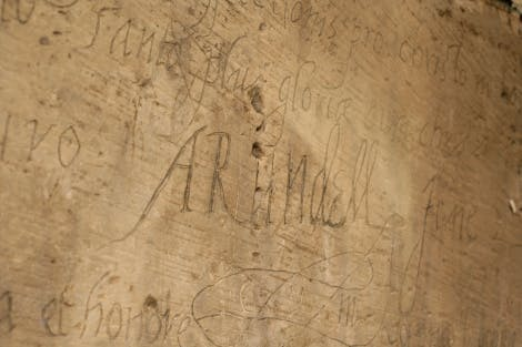 'Arundel' inscription carved into the walls of the upper Beauchamp chamber by Philip Howard, Earl of Arundel, 1587.