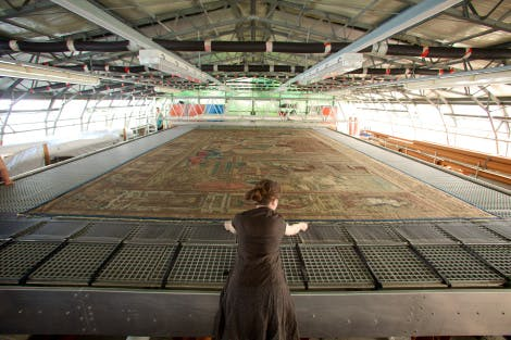 A conservator leans over a large machine where a historic tapestry is being cleaned and restored