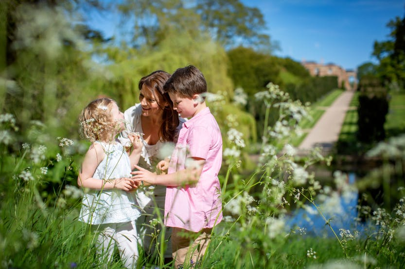 A woman and her two children play in the pond area at Hillsborough Castle and Gardens, with the castle and Yew Tree Walk in the background under a bright blue sky