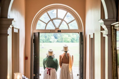 The South Front Hallway, looking south towards the back view of two female Historic Royal Palaces performers. They are wearing early 19th century costume and standing at the open exit doorway.