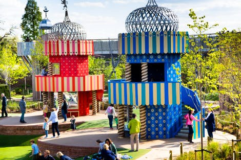 Children and parents play on two red and blue towers - the King's and Queen's Towers - in the sunshine at The Magic Garden