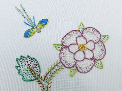 Embroidered dragonfly and rose motif on a white background, inspired by the Bacton Altar Cloth