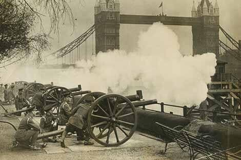 Guns are fired from the Tower of London wharf in front of the Thames with Tower Bridge in the background