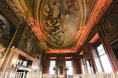 Baroque painted ceiling above a panelled room set up for a wedding, surrounded by historic paintings