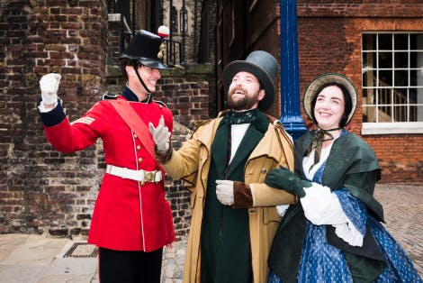 Sergeant Timothy Gowing, in uniform,  and two Victorian visitors, a lady in bonnet and crinoline and a gentleman in a top hat and overcoat, are enjoying Christmas at the Tower in 1858.