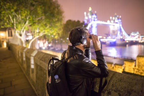 Male participant, from the Nightwatchers experience, using binoculars to take in views of Tower Bridge at night