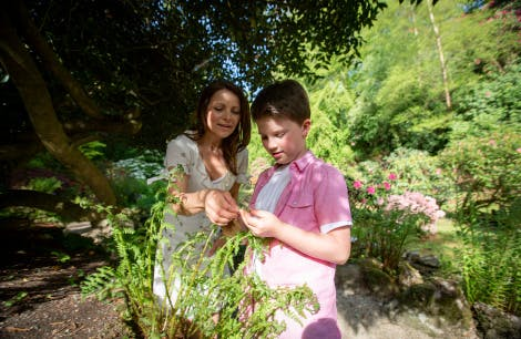 A woman and her two children enjoy The Glen at Hillsborough Castle and Gardens on a bright sunny day