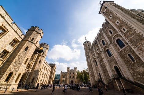 Visitors queue for the Crown Jewels on a sunny day. Around them, from left to right, Waterloo Block, the Royal Fusiliers' Building and the White Tower can be seen with blue sky in the background